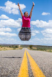 Happy woman jumping over american road Royalty Free Stock Image
