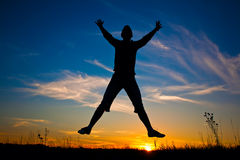 Happy woman jumping over the sunset blue sky Stock Photos