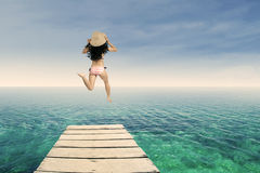 Happy woman jumping at pier 1 Royalty Free Stock Photography