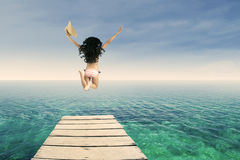 Happy woman jumping at pier Stock Image