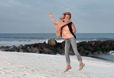 Happy girl jumping playfully on beach in autumn. Royalty Free Stock Photo