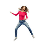 Happy woman jumping and pretending guitar playing Stock Photos
