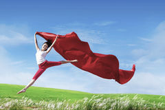 Happy woman jumping with red scarf Stock Photo