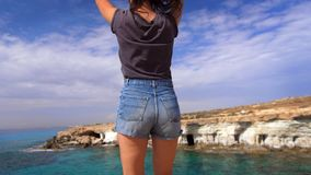 Happy woman jumping at rocky cliff near sea. Joyful girl enjoy holiday. Female legs in shorts jumping on rocky shoreline. Happy woman jumping at rocky cliff near stock video footage