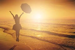 Happy Woman Jumping in Sea beach Sunset silhouette. Royalty Free Stock Image