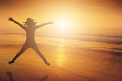 Happy Woman Jumping in Sea beach Sunset silhouette.Copy space Royalty Free Stock Images