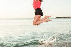 Happy Woman Jumping in Sea Sunrise close-up royalty free stock photos
