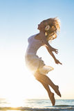 Happy Woman Jumping at the sea. Happy Woman Jumping in the Sea Sunset Stock Photos