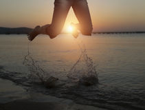 Happy Woman Jumping in Sea Sunset Stock Photos