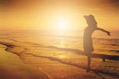 Happy Woman Jumping in Sea Sunset silhouette. Royalty Free Stock Photography