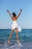 Happy woman jumping at a seaside. Royalty Free Stock Images