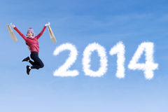 Happy woman jumping with shopping bag. Asian woman jumping beside on the word 2014 on the blue sky Royalty Free Stock Photography