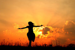 Happy woman jumping and sunset silhouette Royalty Free Stock Images