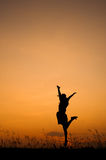 Happy woman jumping and sunset silhouette on relaxing day Stock Images