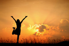 Happy woman jumping and sunset silhouette Stock Images