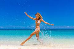 Happy woman jumping on tropical beach Royalty Free Stock Image