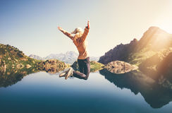 Happy Woman jumping up Flying levitation with lake and mountains on background. Lifestyle Travel emotions concept outdoor Stock Photo