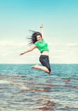 Happy woman jumping in the water of sea Royalty Free Stock Image