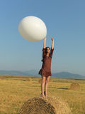 Happy woman jumping white balloon hay stack Stock Photography