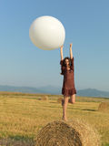 Happy woman jumping white balloon hay stack Royalty Free Stock Images