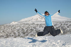 Happy woman jumping at winter mountains, active female enjoying nature, Stock Photography