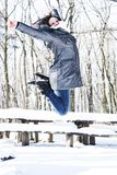 Happy woman jumping in the winter in wood Royalty Free Stock Photography