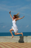 Happy woman jumps in blue sky Stock Images