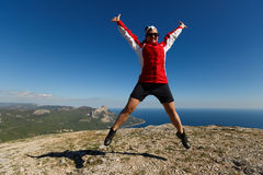 Happy woman jumps on a peak of a mountain in summer time in mountains enjoying the climb with beautiful rocky and sea royalty free stock images