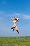 The happy woman jumps in a summer green field Stock Photo