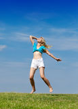 The happy woman jumps in a summer green field against the blue sky Royalty Free Stock Photography