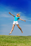 The happy woman jumps in a summer green field against the blue sky..Portrait in a sunny day Royalty Free Stock Photo