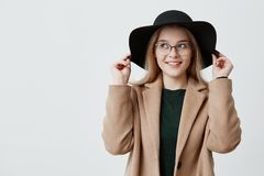 Happy woman with keen eyes and gentle smile wearing retro hat, eyeglasses and coat, holding sides of her hat. Flitry. Happy woman with keen eyes and gentle smile Royalty Free Stock Image