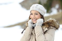 Happy woman keeping warm in winter looking at you. In a snowy mountain royalty free stock images