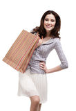 Happy woman keeps striped paper gift bag. Isolated on white Royalty Free Stock Photography