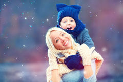 Happy woman and kid embracing under winter snow Stock Photo