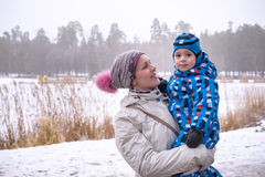 Happy woman and kid embracing under winter snow Royalty Free Stock Image