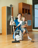 Happy woman and kid with vacuum cleaner Royalty Free Stock Images