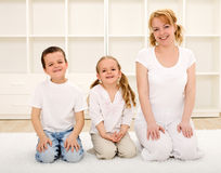 Happy woman and kids indoors sitting on the floor Stock Image