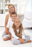 Happy woman and kids sitting in the living room Stock Photography