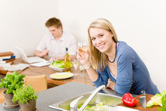 Happy woman kitchen cook enjoy white wine. Happy woman cook enjoy white wine in kitchen, man in background Royalty Free Stock Photo