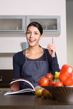 Happy Woman at the Kitchen counter with Recipe Book Royalty Free Stock Photography