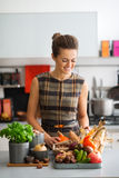 Happy woman in kitchen looking down at autumn vegetables Royalty Free Stock Photography