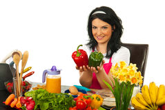 Happy woman in kitchen showing peppers Royalty Free Stock Images