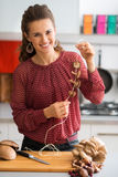 Happy woman in kitchen stringing mushrooms together Royalty Free Stock Image