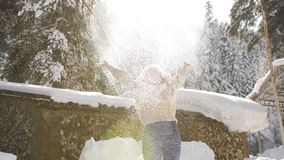 Happy woman enjoys sunny winter morning, toss in the air spinning in snow and sparkling in the sun snowflakes. Happy woman in knit sweater and fur hat enjoys a stock footage