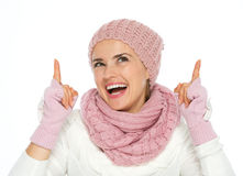 Happy woman in knit winter clothing pointing up Stock Image