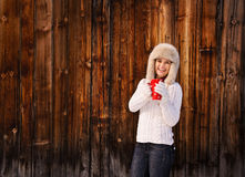 Happy woman in knitted sweater with cup near rustic wood wall Royalty Free Stock Image