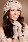 Happy woman in knitted sweater and hat. Studio portrait of a beautiful brunette with long curly hair and brown eyes,beautiful smile,light makeup,wears a knitted stock photography