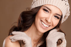 Happy woman in knitted sweater and hat. Studio portrait of a beautiful brunette with long curly hair and brown eyes,beautiful smile,light makeup,wears a knitted royalty free stock photo