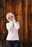 Happy woman in knitted sweater standing near rustic wood wall Stock Images